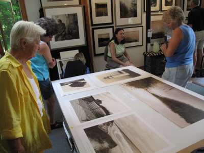 Visitors on a previous Rock River Artists tour admire Chris Triebert's photographs. Triebert and her partner, Carol Ross, a graphic designer, share their studio in South Newfane.