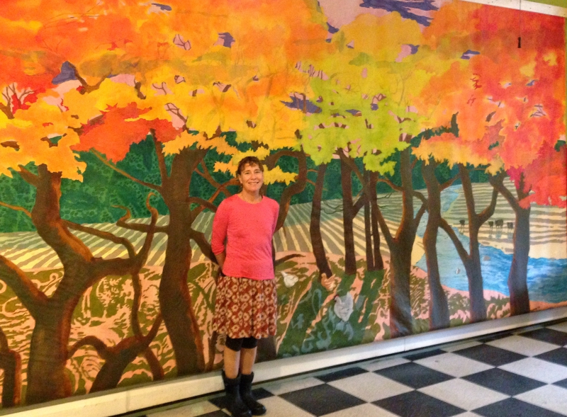 Michelle Ratté stands in front of her painted curtain at Main Street Arts in Saxton's River