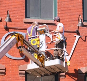 Workers affix Community College of Vermont and Vermont Technical College signage to the front of the building