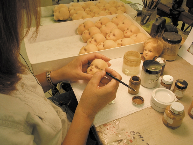 An employee at the R. John Wright Company adds meticulous detail to a doll's facial features.