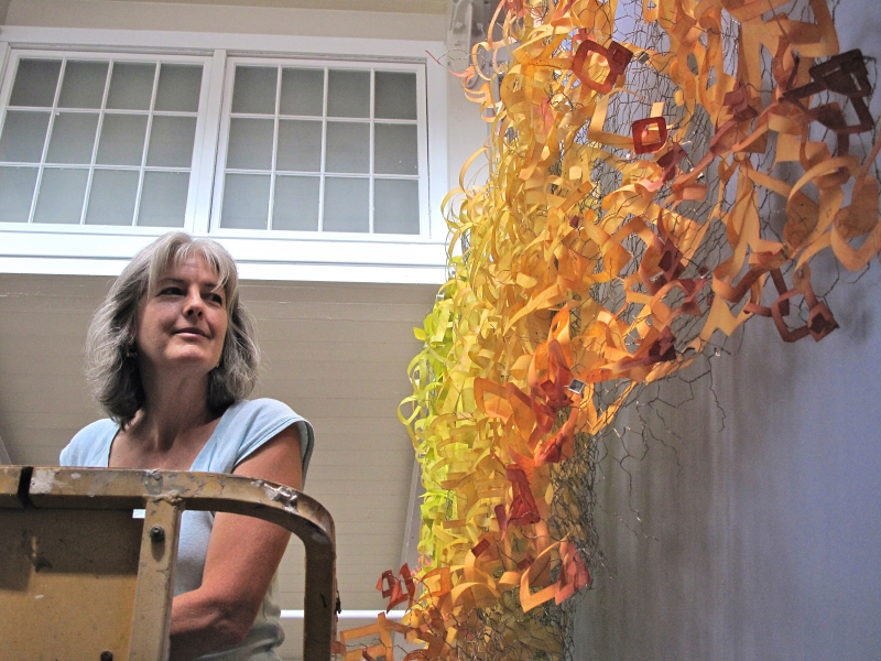 "Artist Carolyn Enz Hack with her work, ""Sowing Good Will,"" 2012. Wire, Hi-tec kozo paper, mixed media. Approx. 55 in. x 124 in. x 15 in."