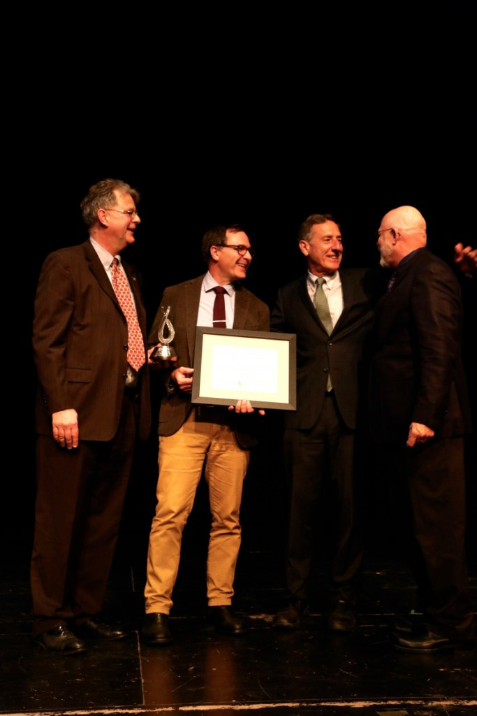 Eric Aho, holding award, is congratulated by Alex Aldrich, executive director of the Vermont Arts Council; Governor Peter Shumlin; and Bob Stannard, chair of the arts council board.